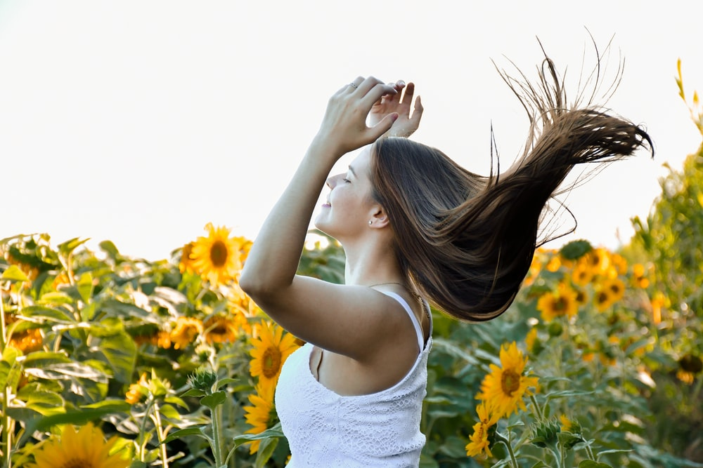 woman in white tank top standing on yellow flower field during daytime