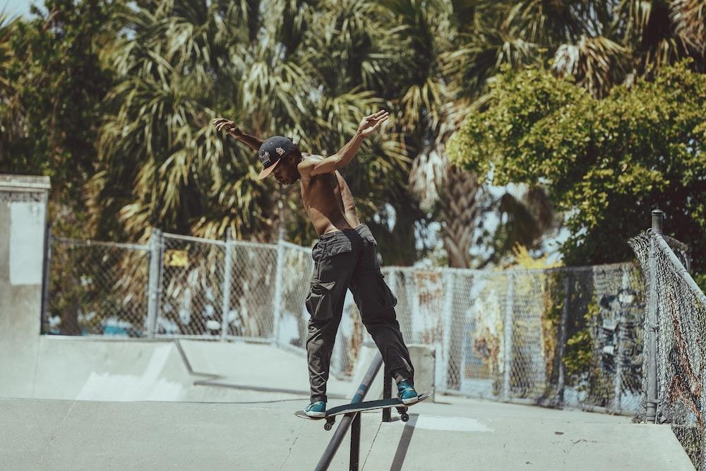 man in black tank top and black pants doing skateboard stunts