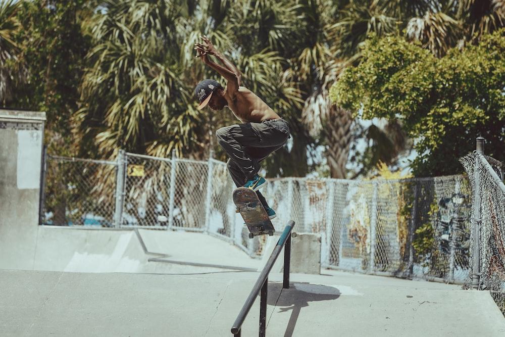 man in black jacket and black pants doing skateboard stunts on black and blue skateboard ramp
