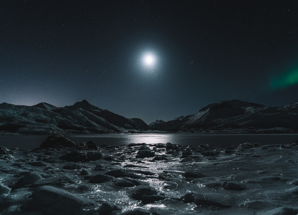 snow covered mountain during night time