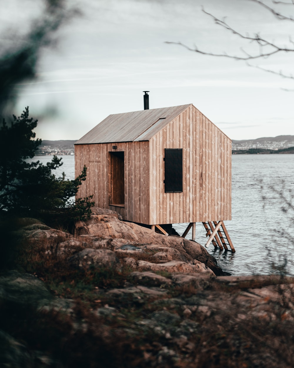brown wooden house on brown rock near body of water