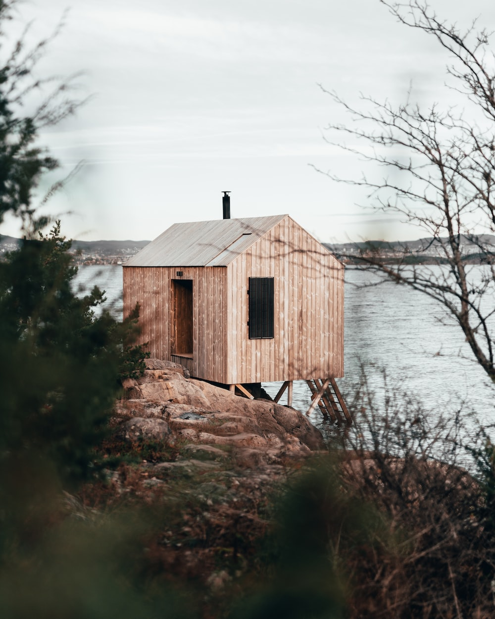 brown wooden house near body of water