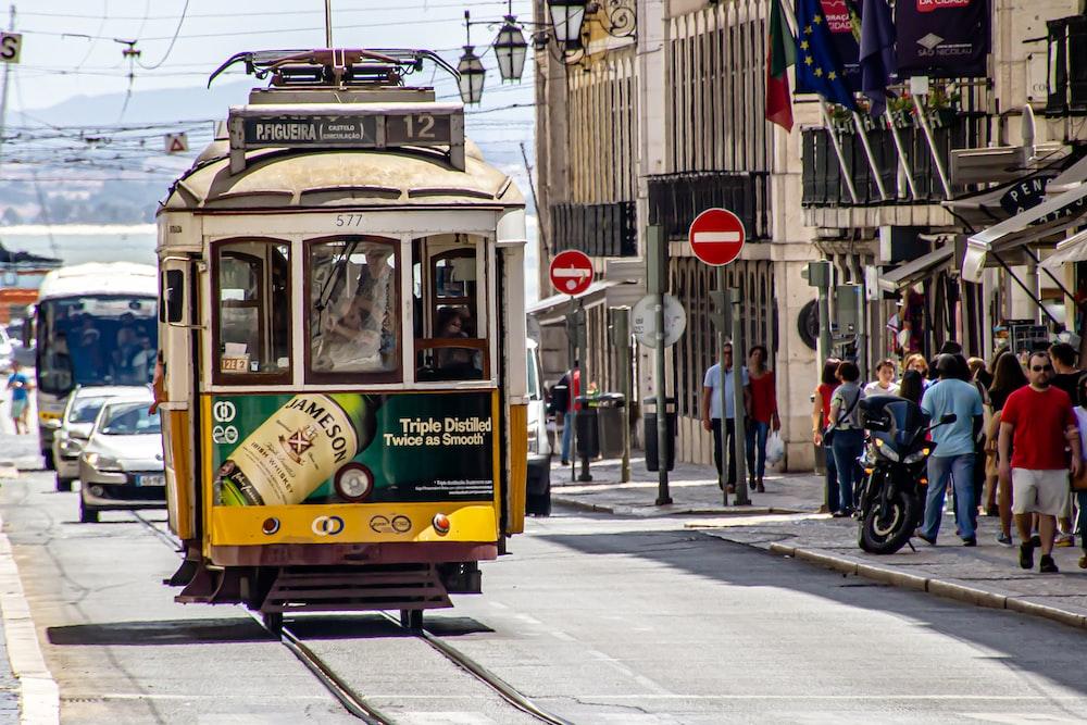 people walking on sidewalk near yellow tram during daytime