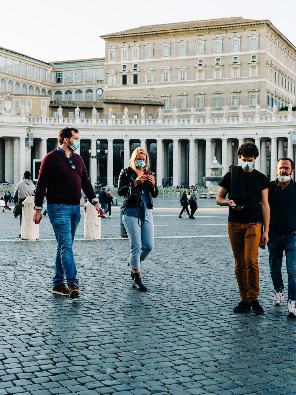 3 men and woman walking on street during daytime