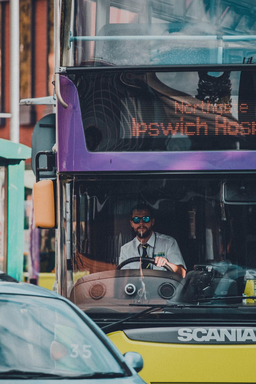 man in black jacket sitting on red bus during night time