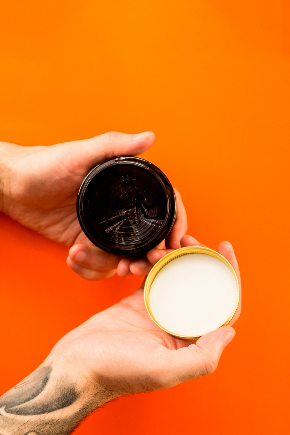 person holding black and brown round container