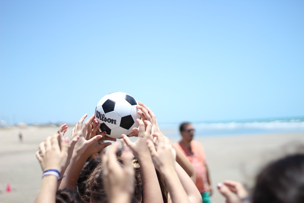 people holding white and black soccer ball under blue sky during daytime