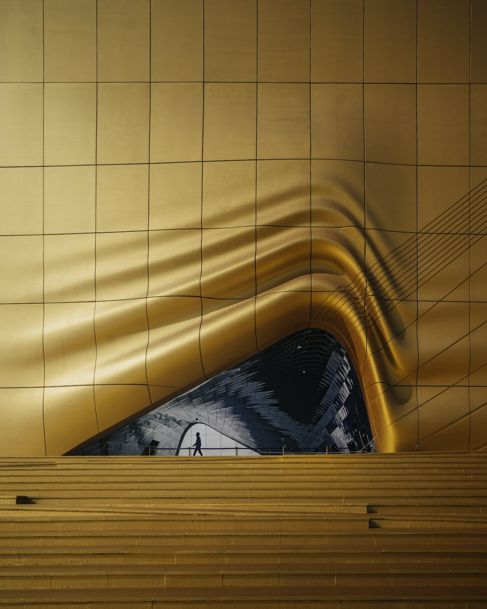 person in black and white shirt lying on yellow bed