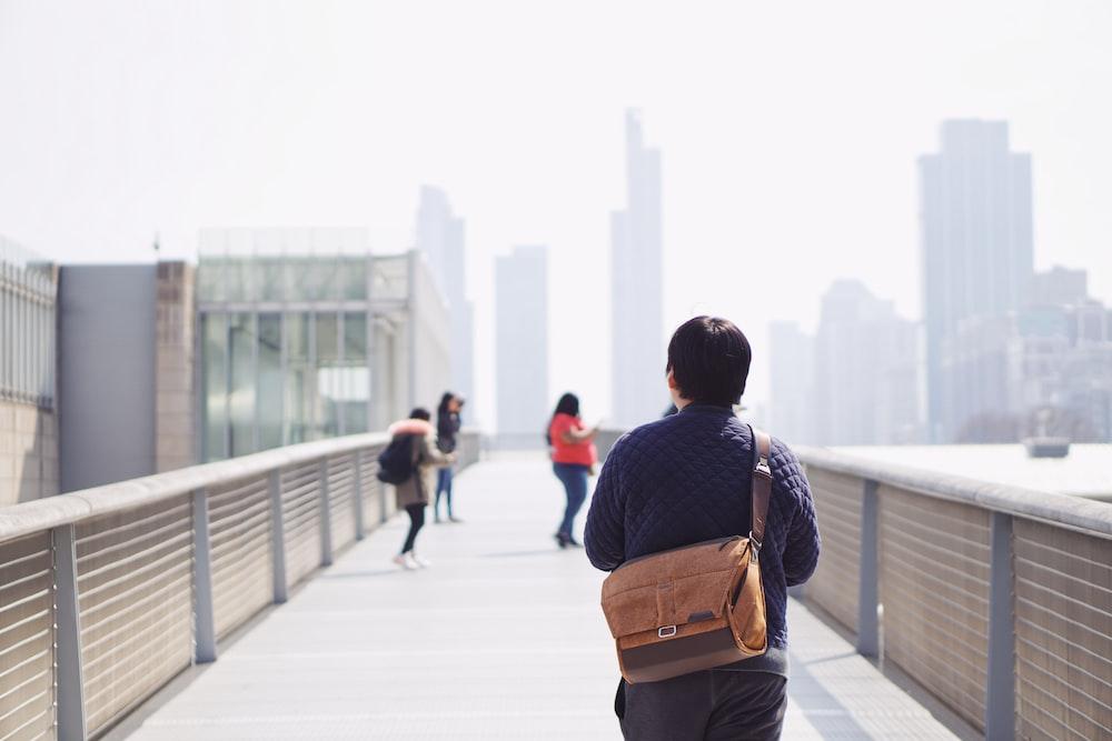 man in black and brown backpack walking on sidewalk during daytime