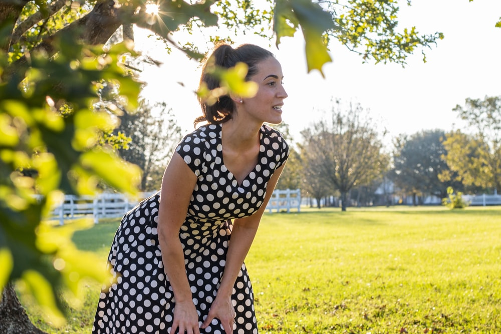 woman in black and white polka dot dress standing on green grass field during daytime