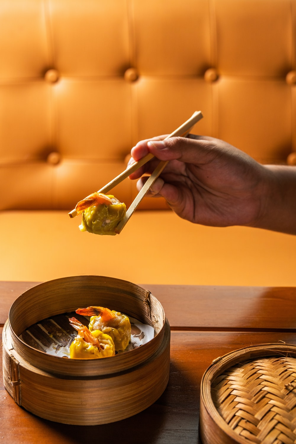 person holding chopsticks with vegetable salad in bowl