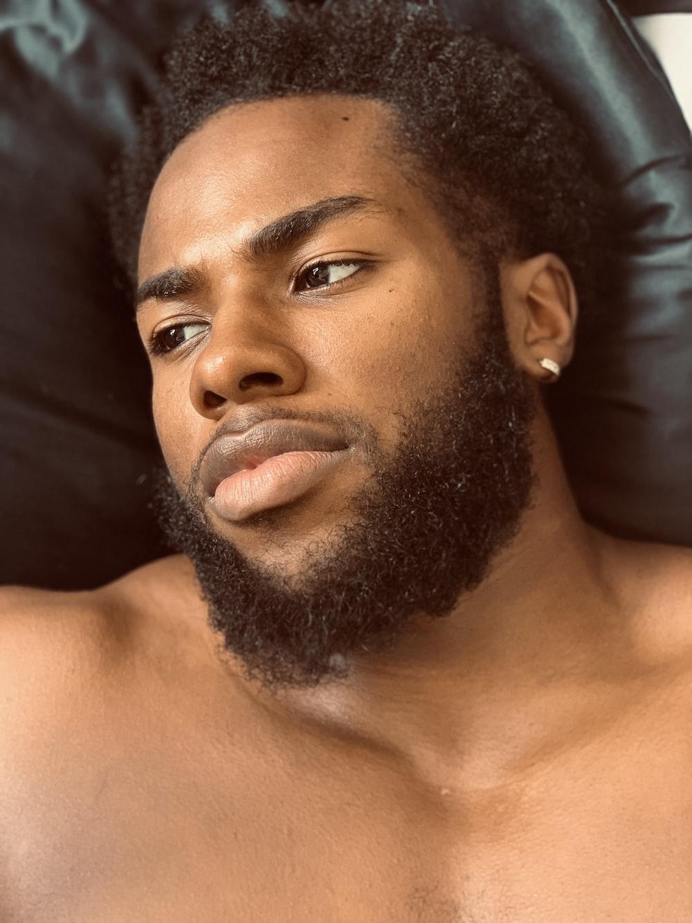 topless man lying on black textile