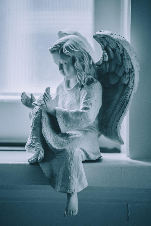 angel ceramic figurine on black table