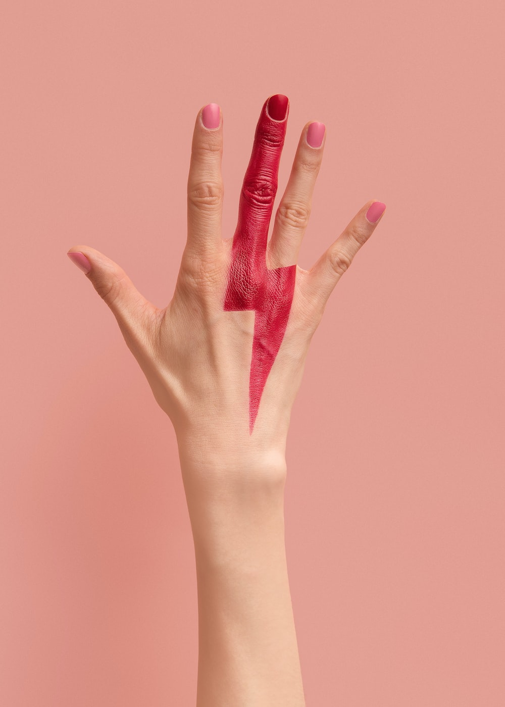 person with pink manicure on pink surface