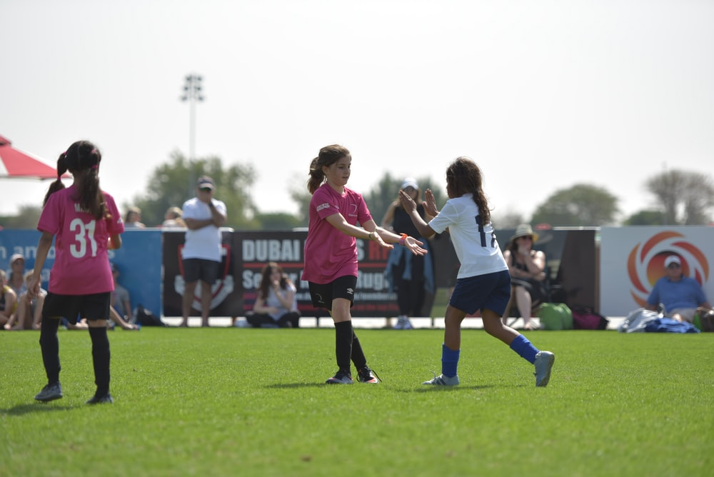 group of women playing soccer during daytime