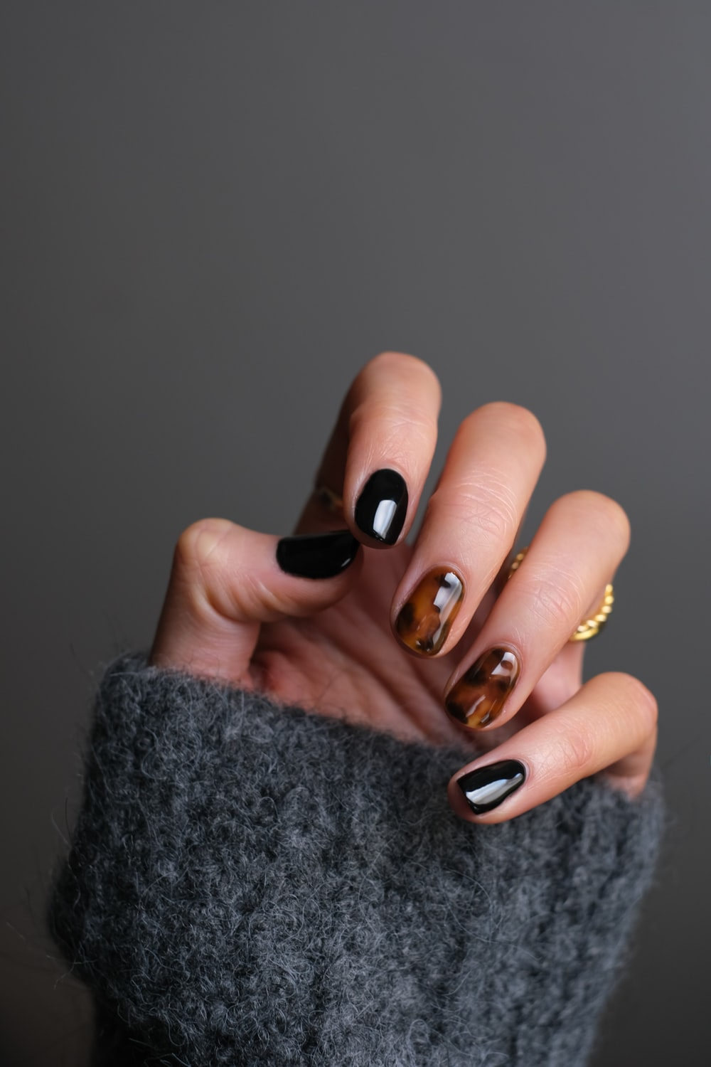person wearing gold ring holding black textile