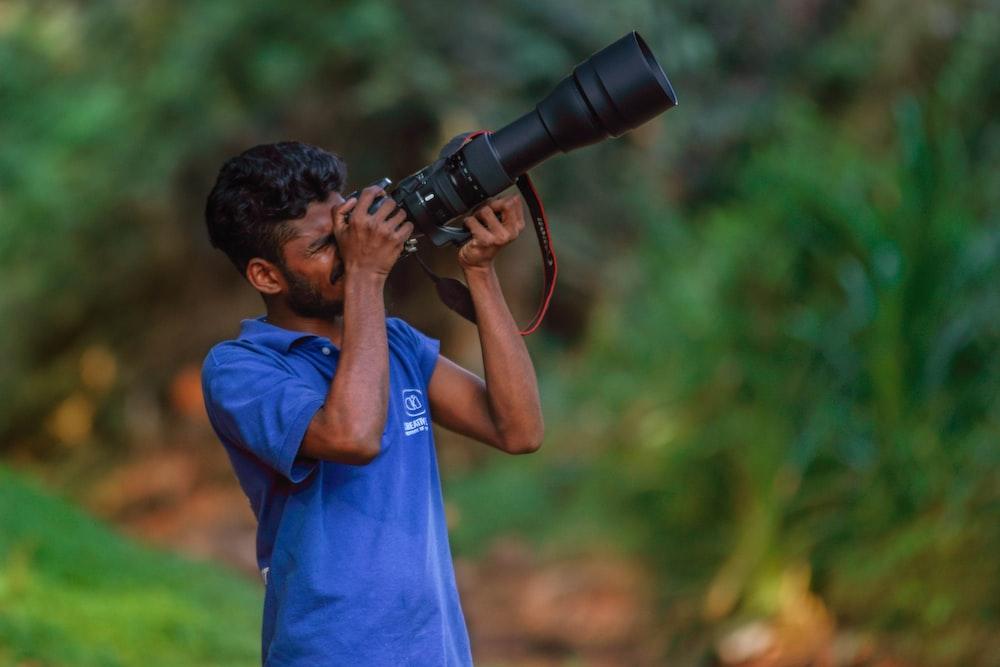 man in blue t-shirt holding black dslr camera