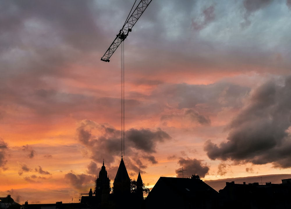 silhouette of crane under cloudy sky during sunset