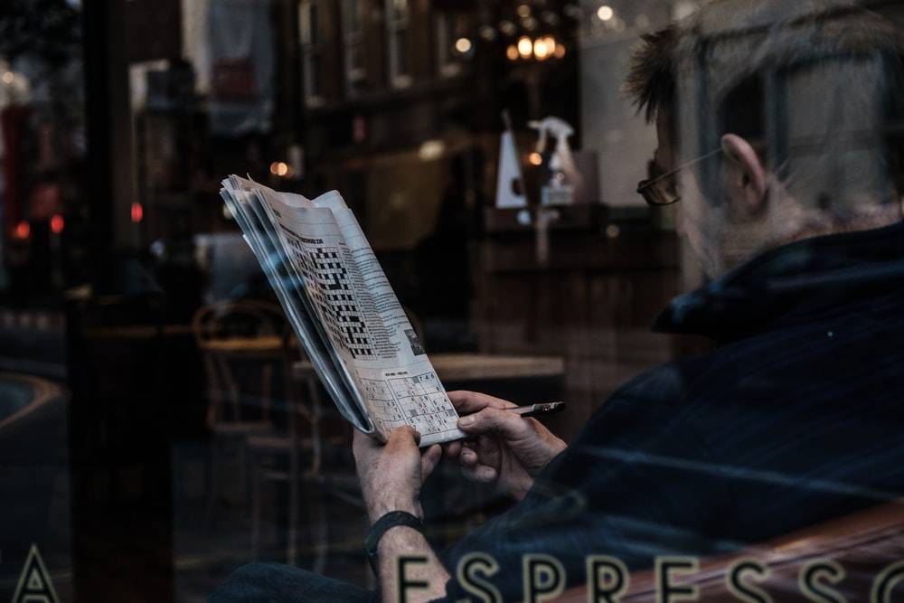 person reading newspaper during night time