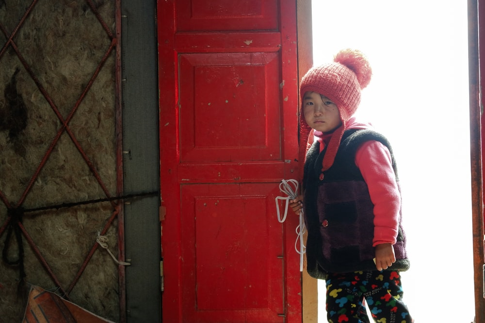 boy in red and blue jacket standing beside red wooden door