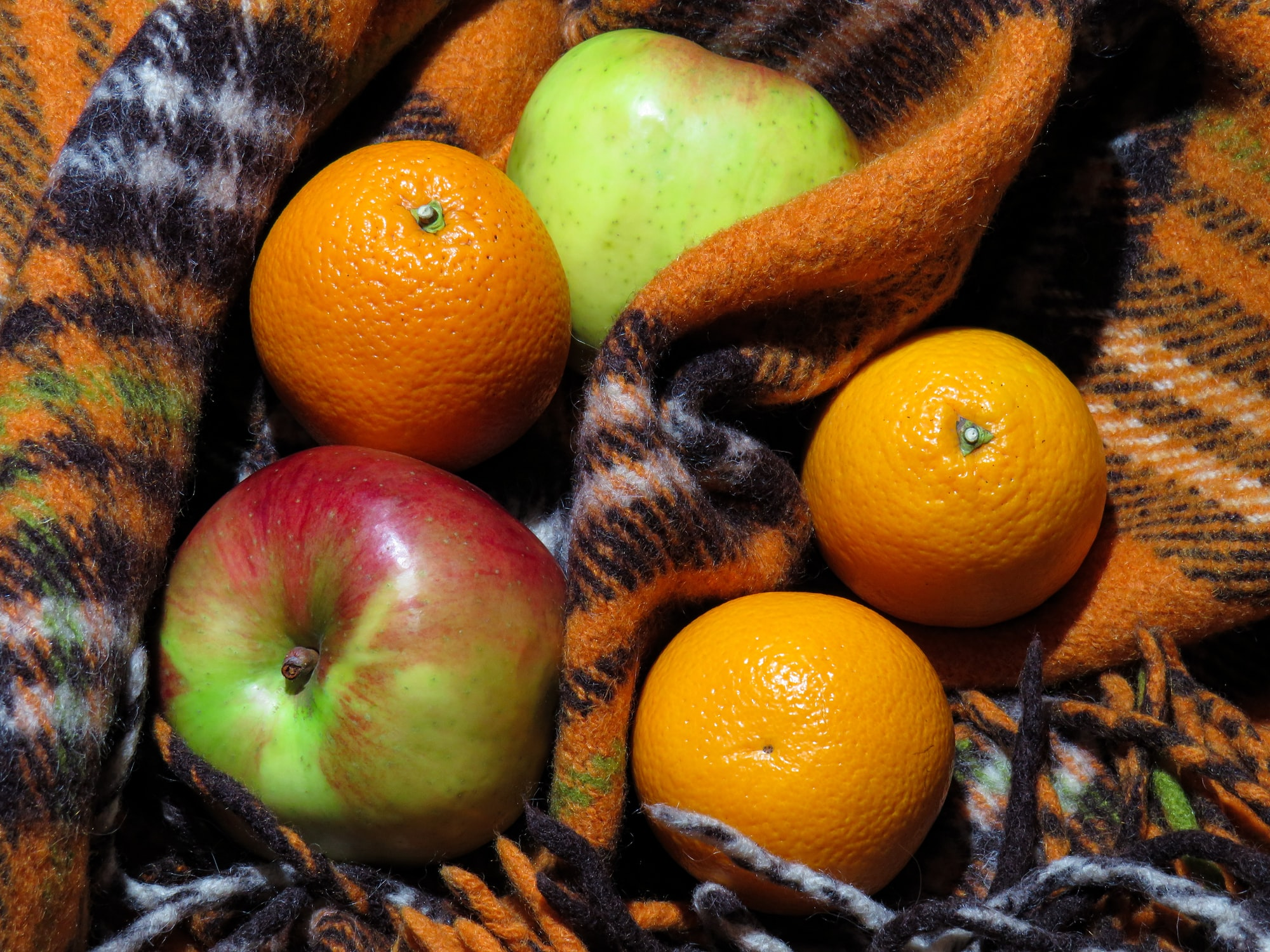 A warm plaid and tasty oranges and apples.