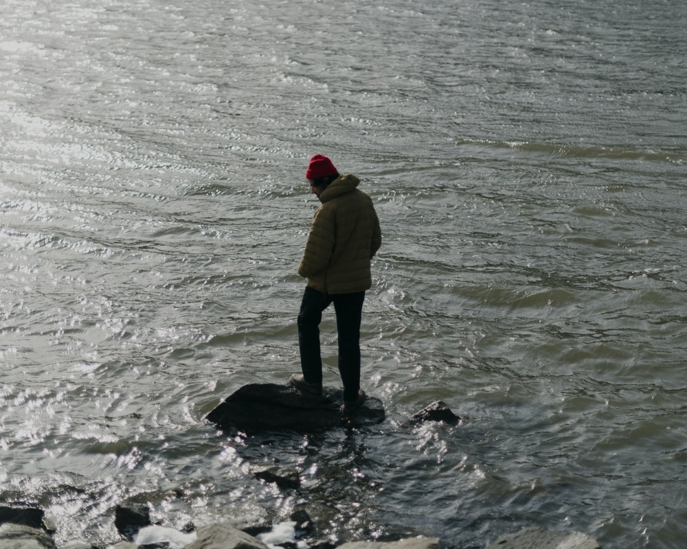 man in yellow hoodie standing on water during daytime