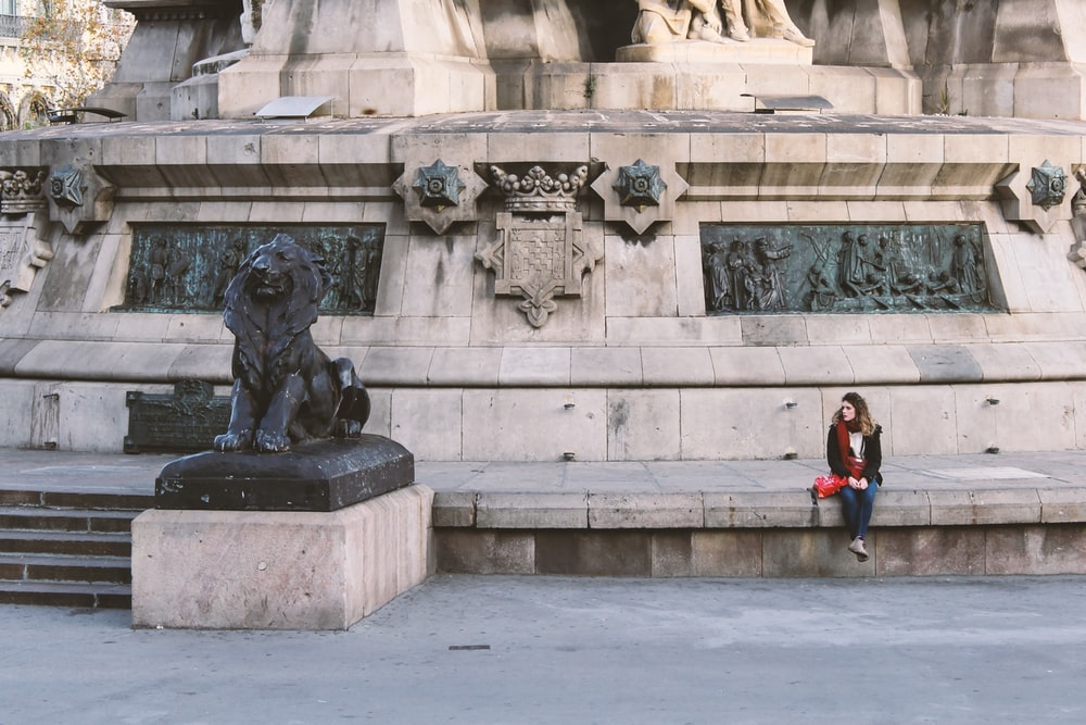 woman in red jacket standing near gray concrete statue during daytime