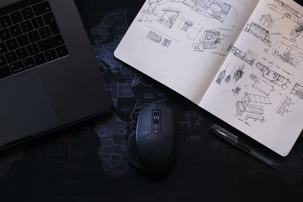 black corded computer mouse on white printer paper