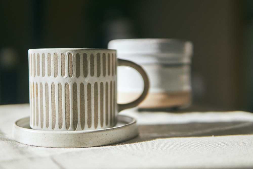 white ceramic mug on white textile