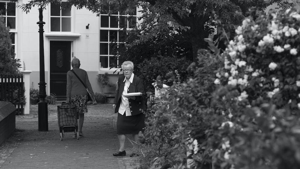 grayscale photo of 2 women standing on sidewalk