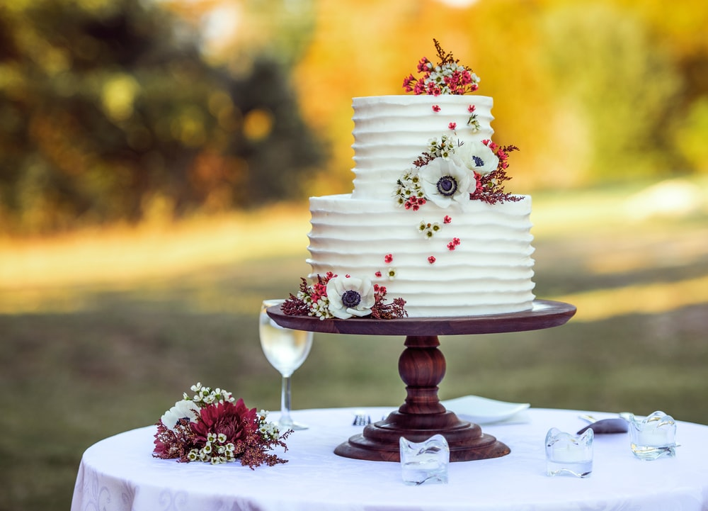 white and red floral cake on brown wooden stand