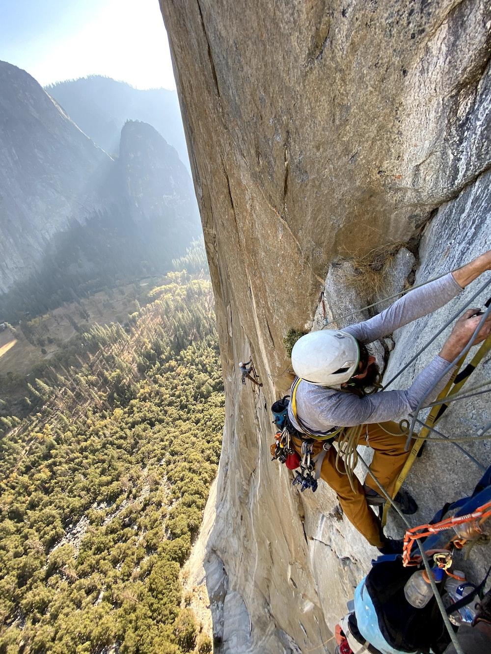 man in white helmet climbing mountain during daytime