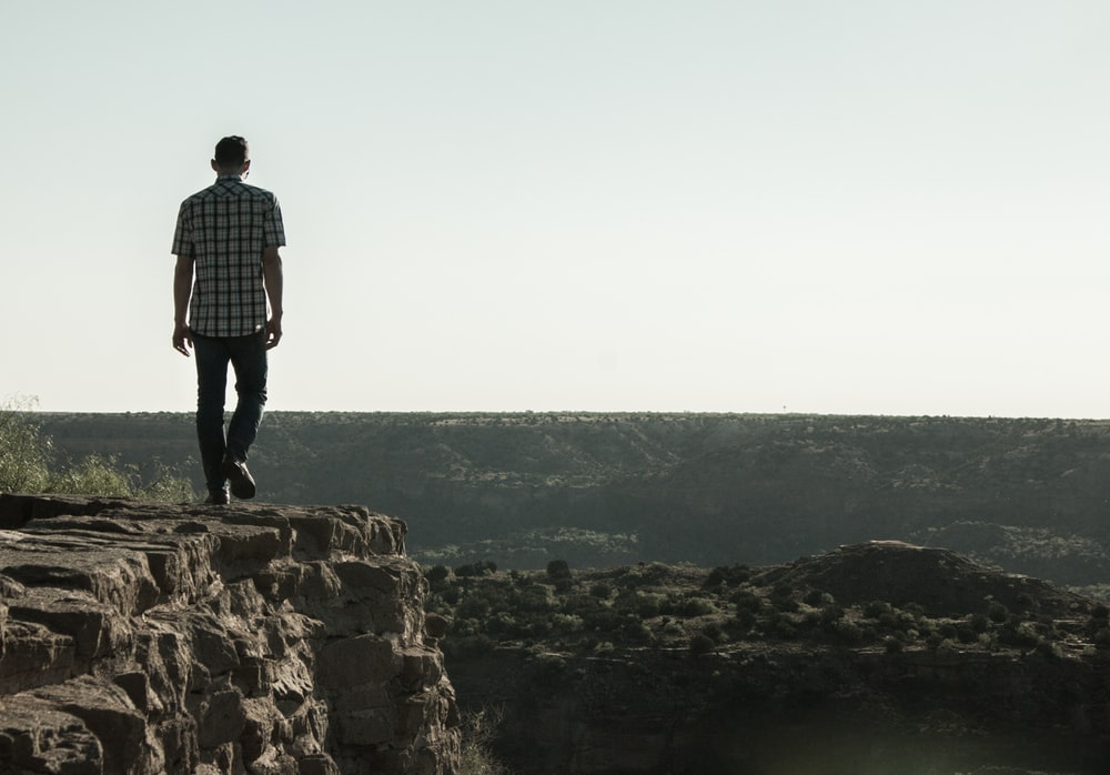 man in white and black checkered dress shirt standing on brown rock formation during daytime