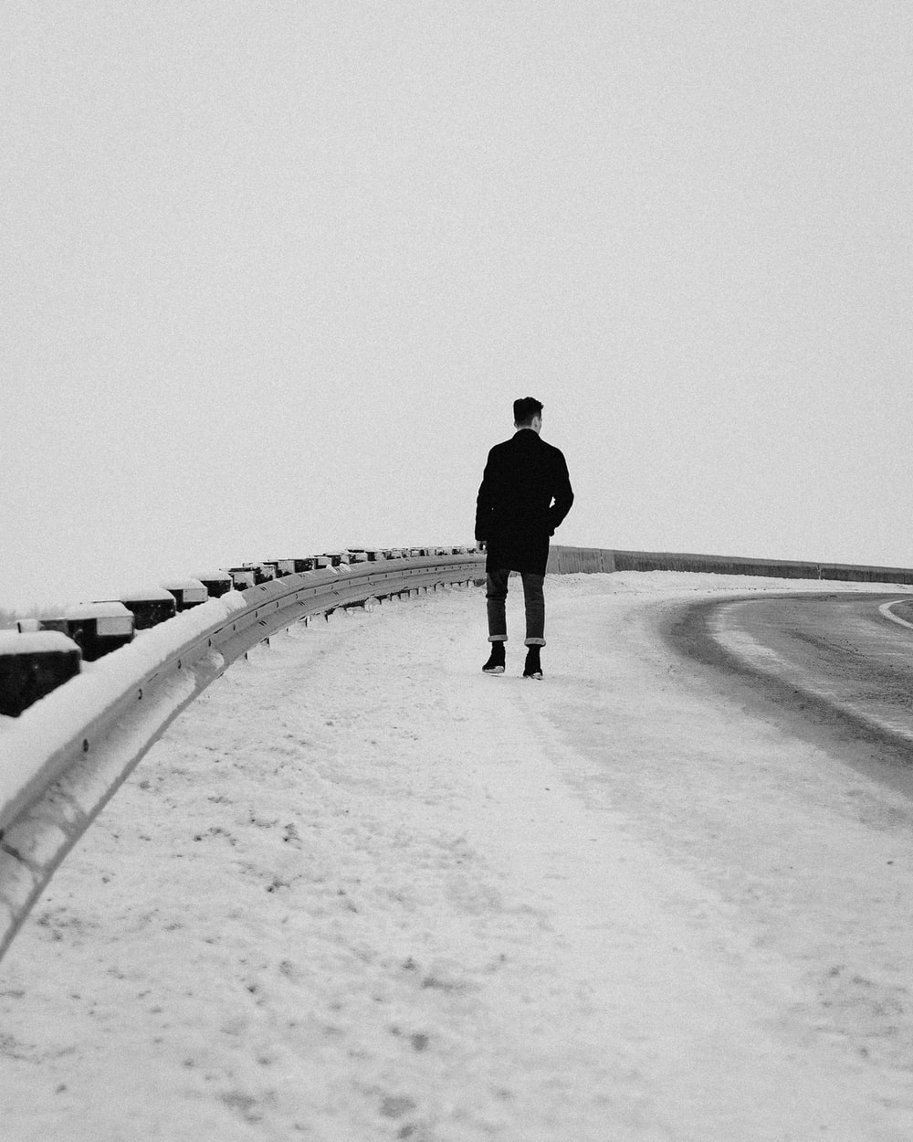 man in black jacket walking on snow covered road during daytime
