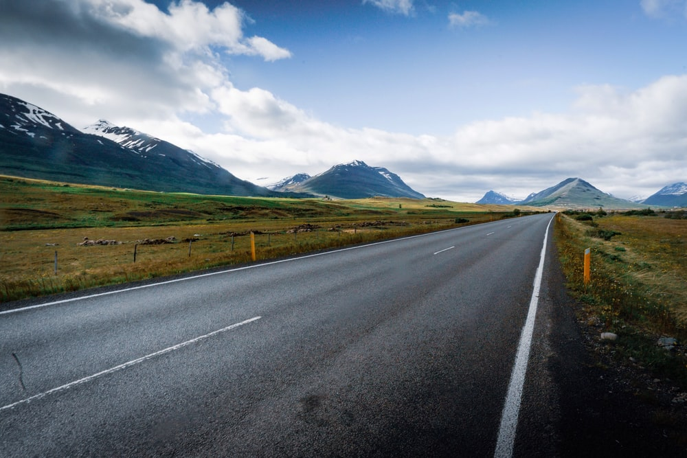 gray concrete road near green grass field and mountains under blue sky and white clouds during