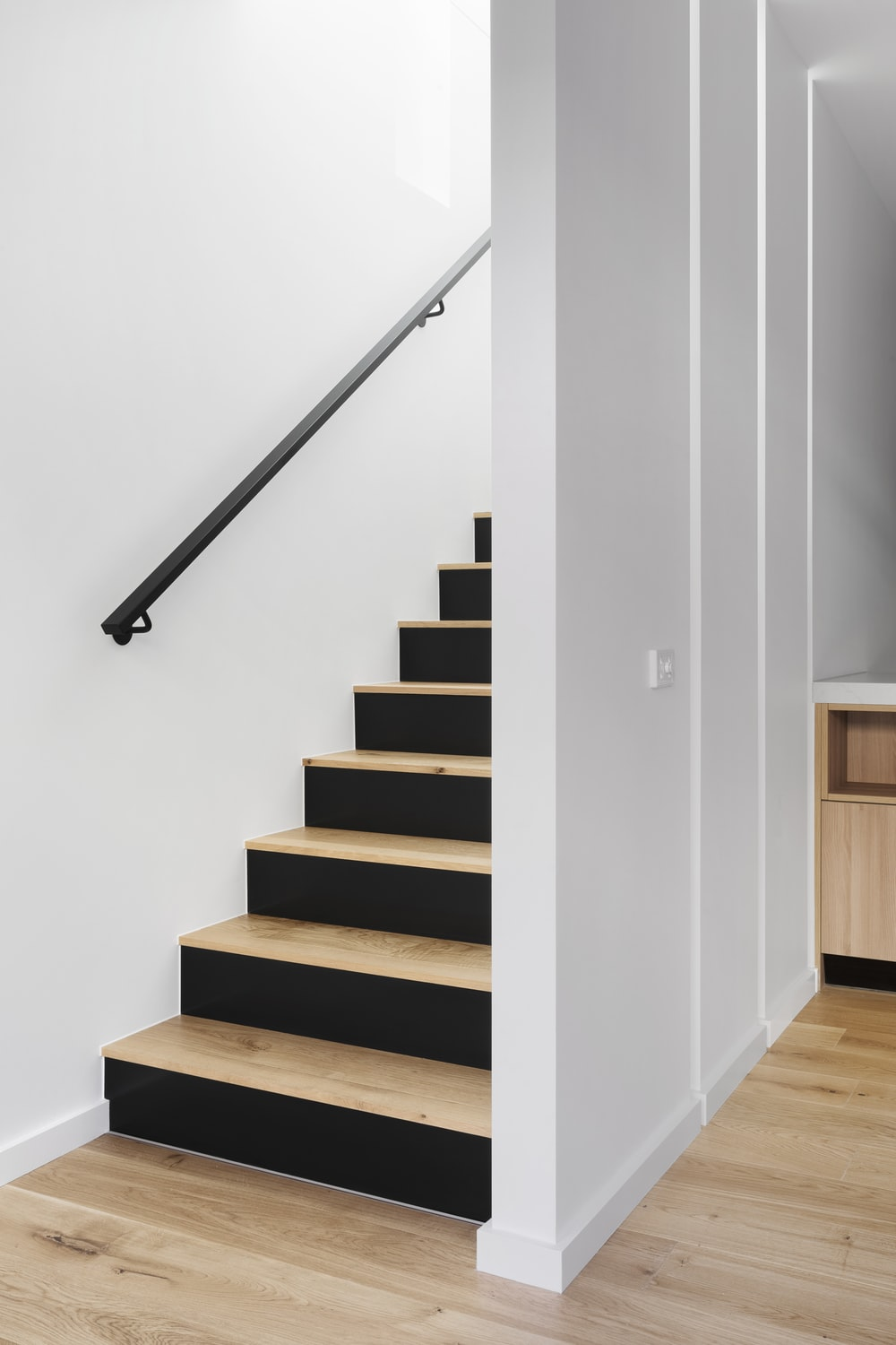 white wooden staircase with stainless steel railings