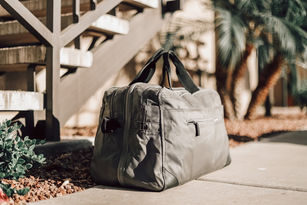 gray leather backpack on white concrete floor