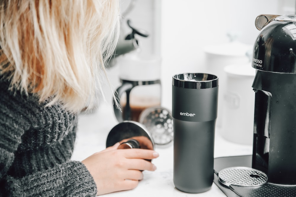 woman in gray sweater holding silver and black travel mug