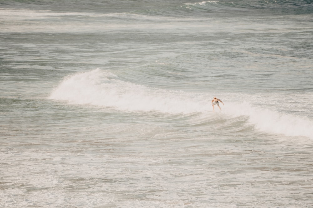 2 person surfing on sea waves during daytime