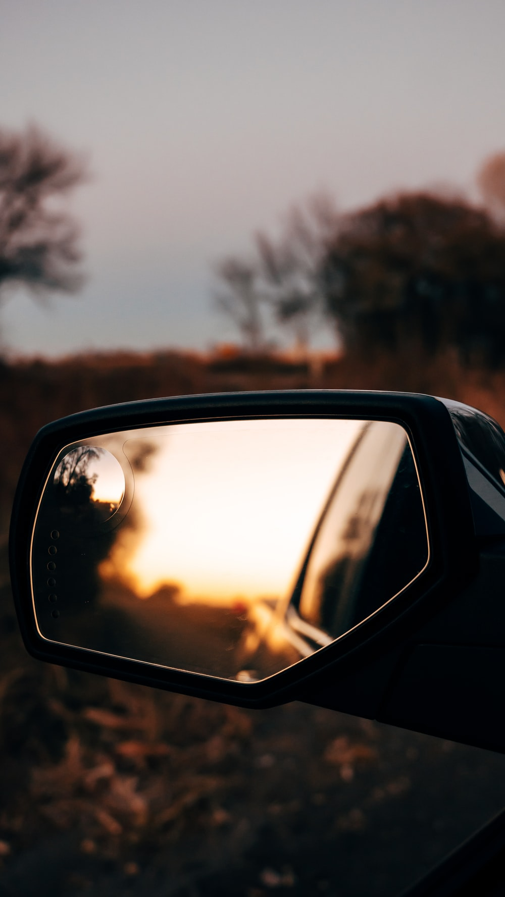 car side mirror with reflection of trees on road during daytime