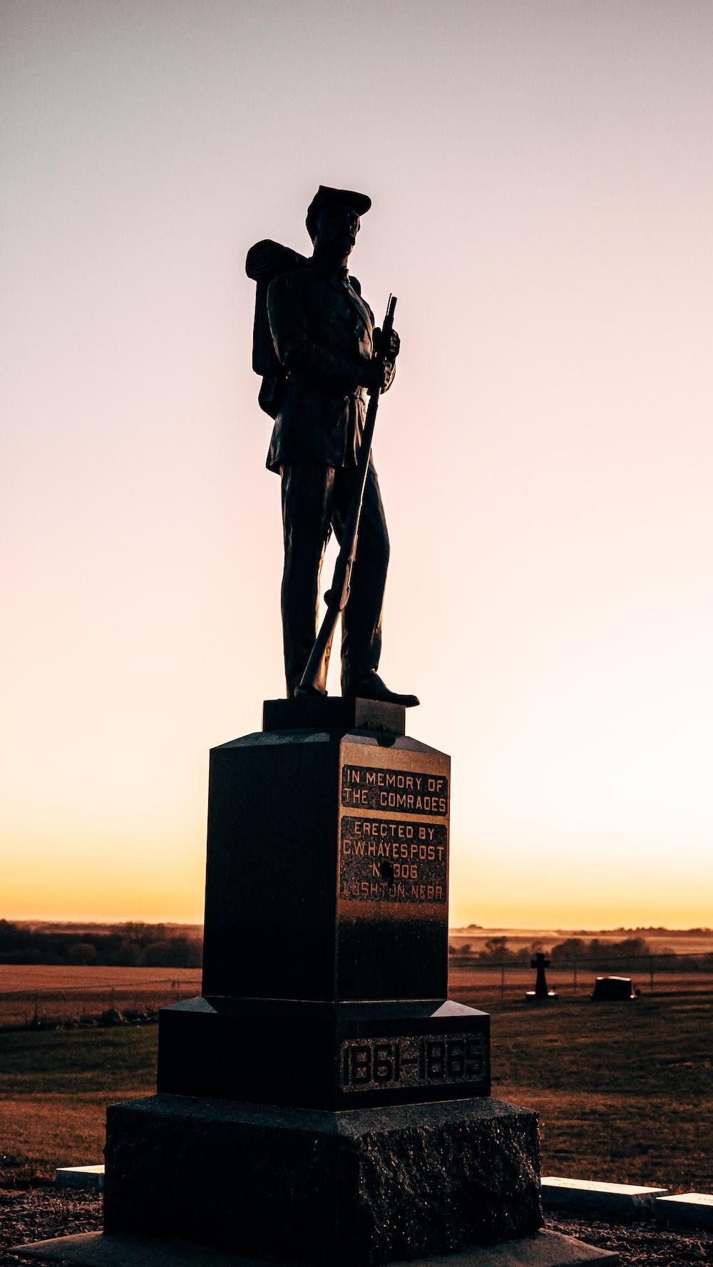 man holding rifle statue during daytime