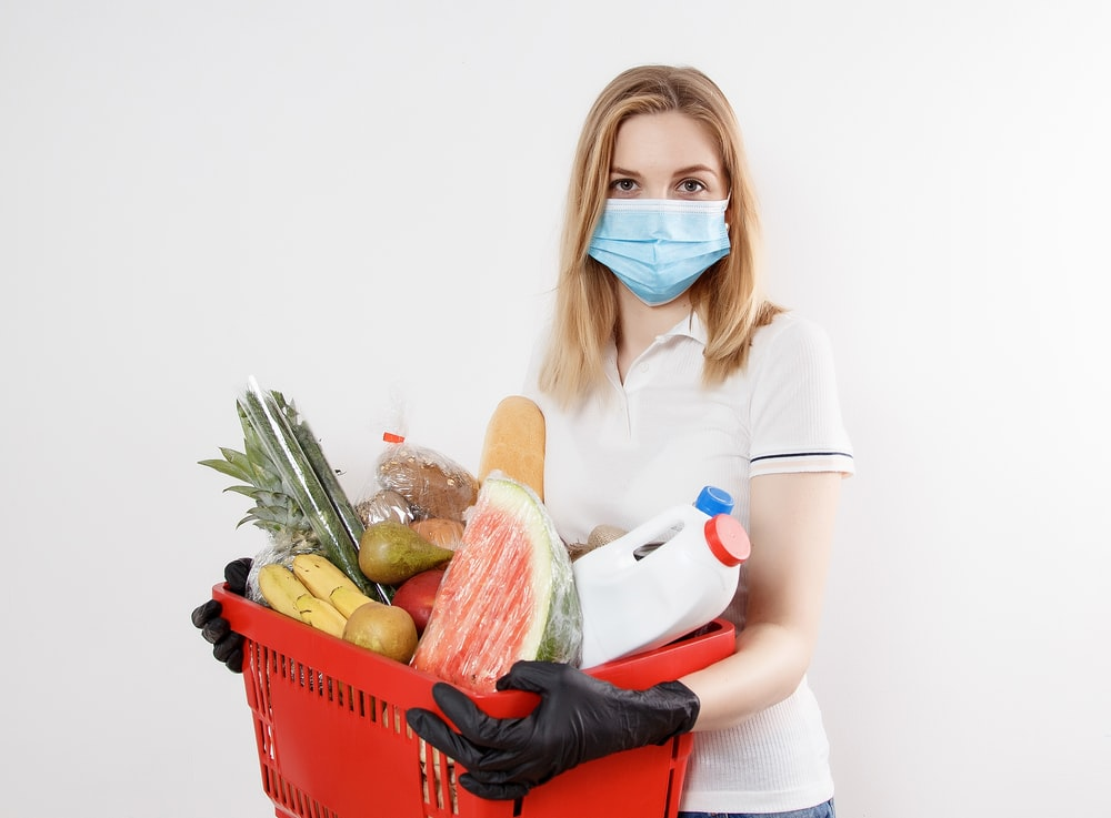 woman in white shirt and blue denim jeans sitting on red plastic laundry basket