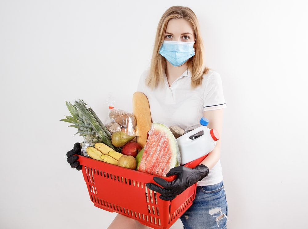 woman in white long sleeve shirt and blue denim jeans holding red plastic basket with fruits