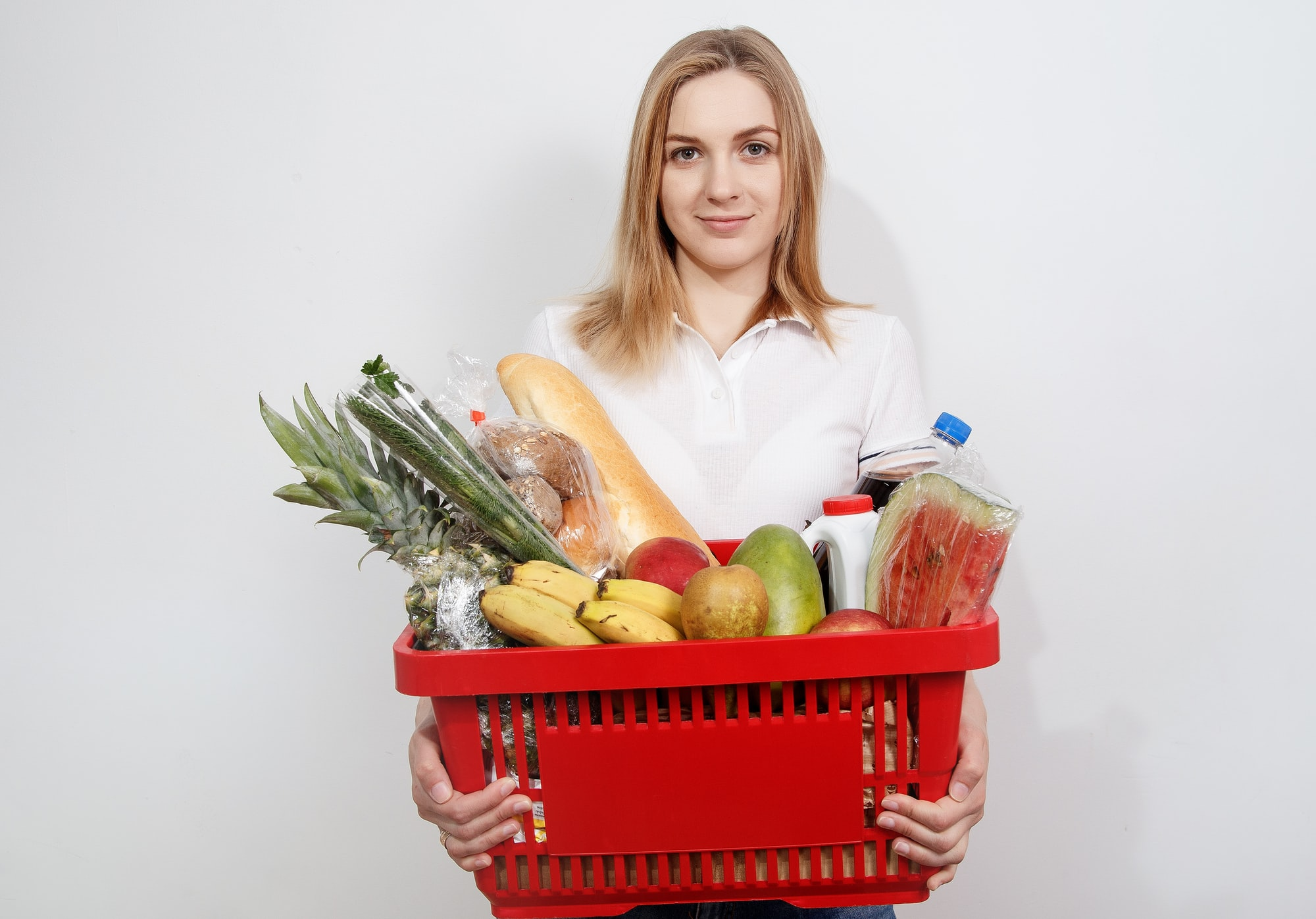 Young woman with goods in basket. The girl made a purchase. Girl holding a basket of groceries. Vegetables