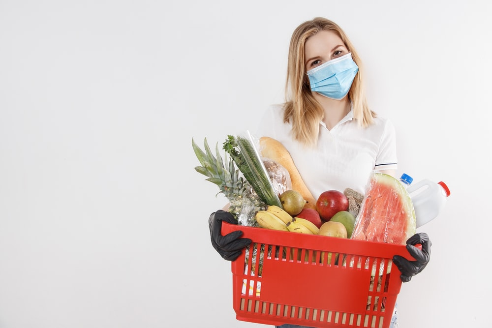 woman in white long sleeve shirt holding red plastic basket with fruits