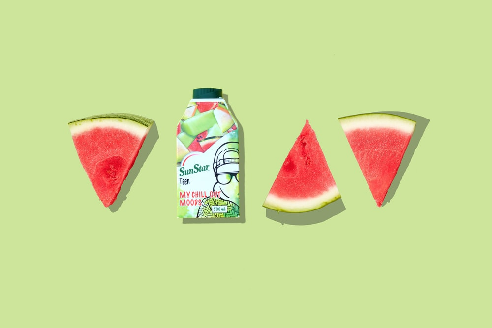 green and white labeled bottle beside sliced watermelon