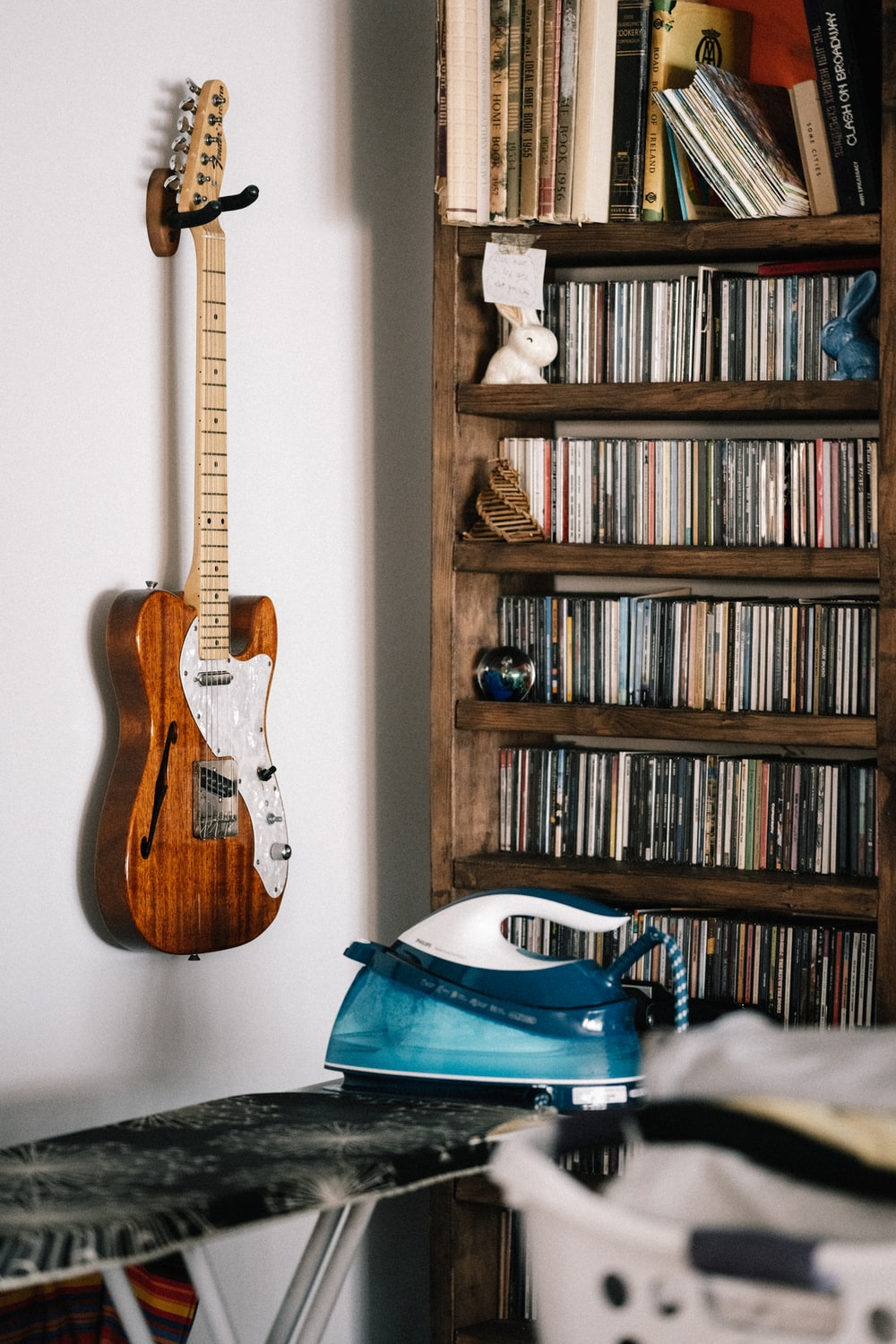 brown and white electric guitar on brown wooden shelf