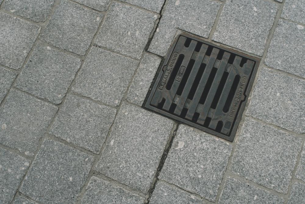 black metal door mat on gray concrete floor