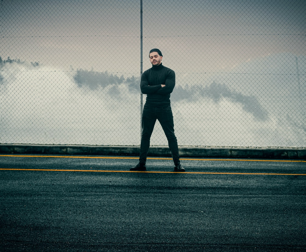 man in black jacket standing on gray asphalt road during daytime