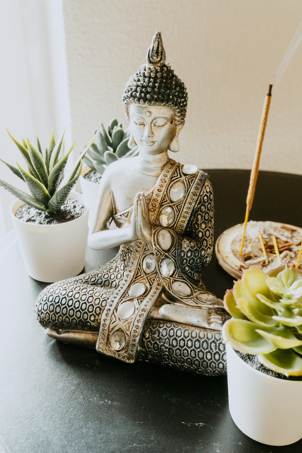 gold buddha figurine beside white ceramic cup with brown liquid